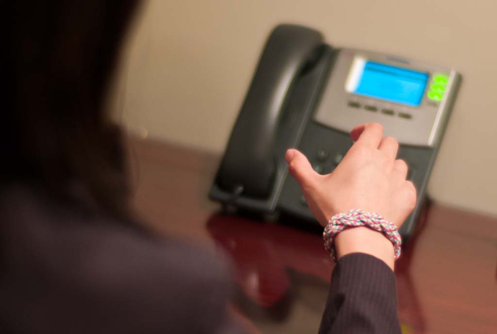Image Of Person Wearing Friendship Bracelet About To Answer Phone